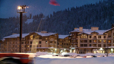 A snowplow passes in front of a hotel in a mountain resort Stock Video Footage