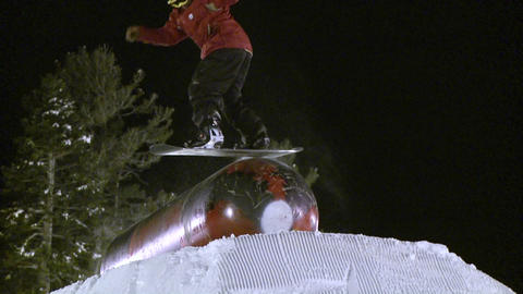 A snowboarder slides on top of a metal cylinder Footage
