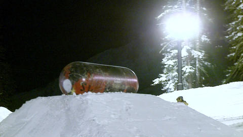 A snow boarder performs a stunt on a metal cylinder Stock Video Footage