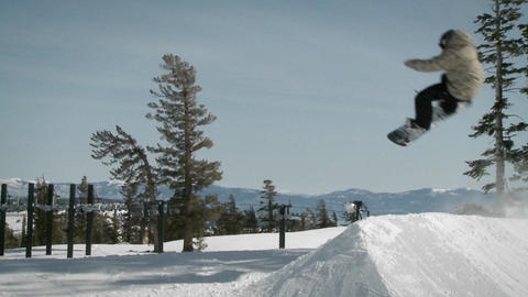A snowboarder makes a jump off a mound of snow Footage