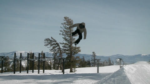 A snowboarder makes a jump off a mound of snow Stock Video Footage