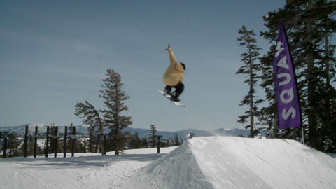 A snow boarder hits a bank of snow and gets air Stock Video Footage