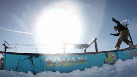 A snowboarder makes a slide and a jump Footage