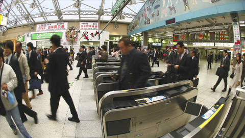 Passengers walk through JR turnstiles in Ueno Station, Tokyo, Japan Footage