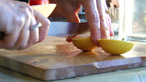 A woman slices a lemon on a wooden cutting board Footage