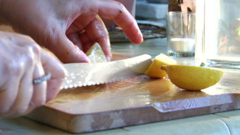 A woman slices a lemon on a wooden cutting board Stock Video Footage