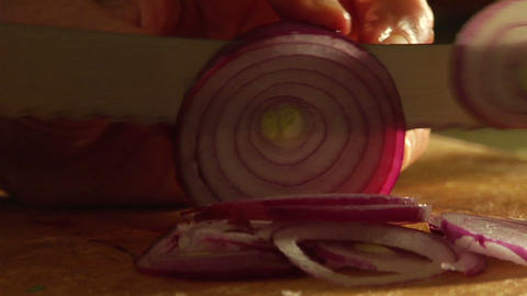A man slices a red onion on a cutting board Footage
