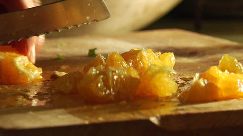 A woman slices an orange on a cutting board Footage