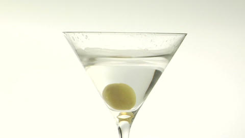A green olive is dropped into a martini Stock Video Footage