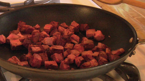 Chunks of beef cook in a frying pan Stock Video Footage