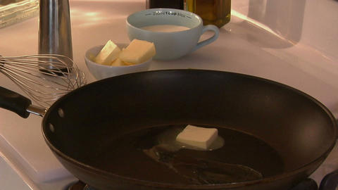 A cube of butter melts in a skillet Footage