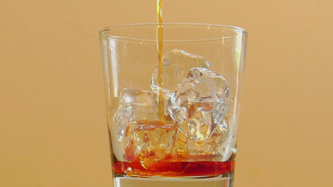 Liquor is poured into a glass with ice Stock Video Footage