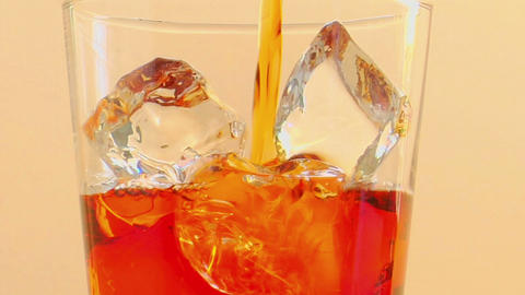 Tilt up to as liquor is poured into a glass with ice Footage