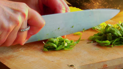 A woman chef preps a salad by chopping basil on a wooden cutting board Footage