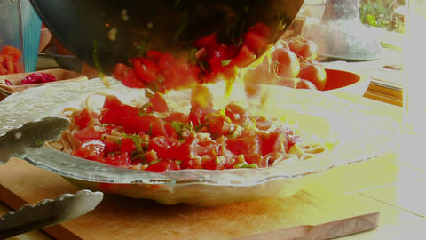A woman chef prepares a meal by pouring fresh cooked sauce onto a steaming bowl of pasta Footage