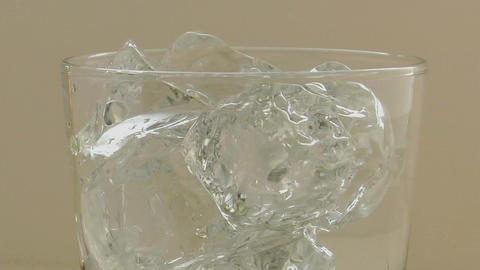 Clear sparkling water poured over ice cubes into a clear... Stock Video Footage