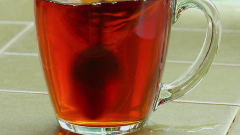 Sugar poured into a clear glass cup of tea and stirred... Stock Video Footage