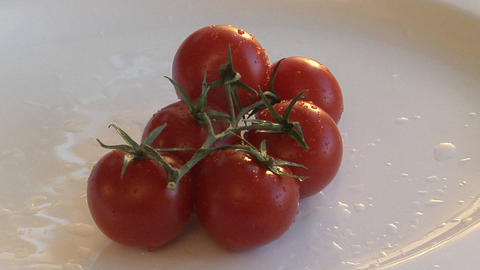 A slow zoom in on a red, ripe tomatoes on a white plate Stock Video Footage