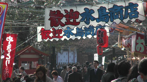 Banners, lanterns and pedestrians in Ueno Park during the cherry blossom season in Tokyo, Japan Footage