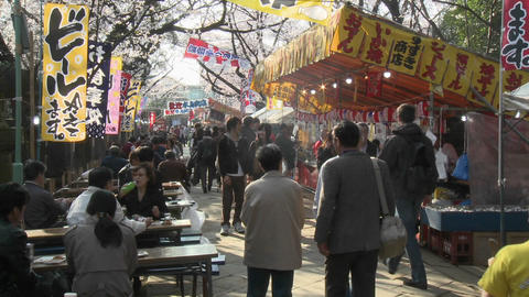 Food stalls and pedestrians in Ueno Park during the cherry blossom season in Tokyo, Japan Footage