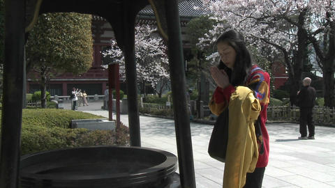 A woman prays at a temple in the Senso-ji complex, Asakusa, Tokyo, Japan Footage