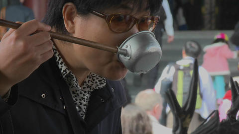 A woman drinks from a ladle used in a purification ritual... Stock Video Footage