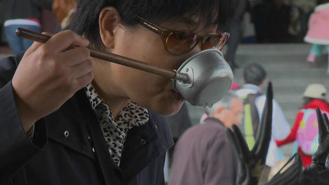 A woman drinks from a ladle used in a purification ritual at the Senso-ji Temple complex in Asakusa Footage