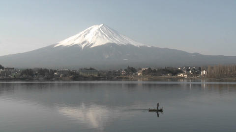 Mt. Fuji rises above a fisherman on Lake Kawaguchi, Japan Stock Video Footage