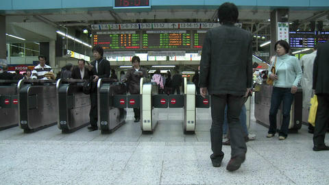 Commuters pass through the turnstiles in Ueno station... Stock Video Footage