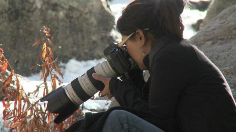 A woman photographs a frozen stream in the Sierra Nevada... Stock Video Footage