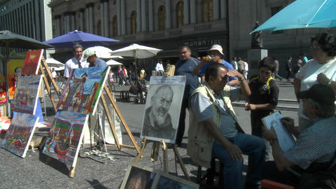 A street artist paints a portrait in the Plaza de Armas, Santiago, Chile Footage