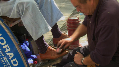 A shoe shine on Paseo Ahumada, a pedestrian street in downtown Santiago, Chile Footage
