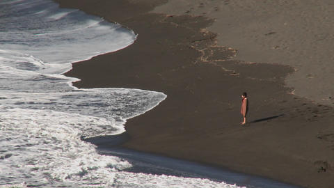 A young child confronts the surf on the beach near Buchupureo, Chile Footage