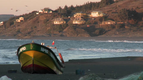 A fishing boat and surfer on the beach at Curanipe, Chile Footage