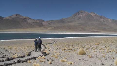 Hikers near the shore of Laguna Miniques high above San Pedro de Atacama, Chile Footage