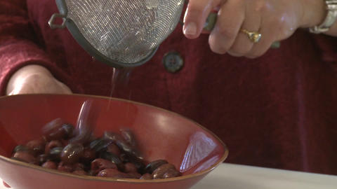 A woman pours olives from a strainer into a bowl Footage