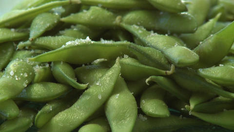 Close up pan of salted organic soy bean pods Footage