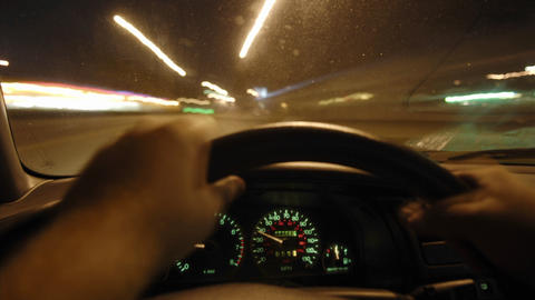 A person drives a car through bright city streets Footage