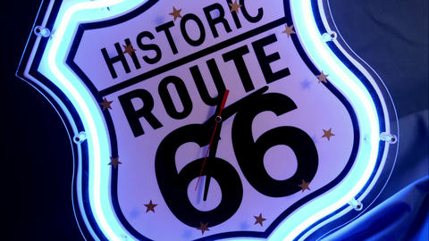 "Clock hands spin on a neon Historic Route 66"" clock face Stock Video Footage"
