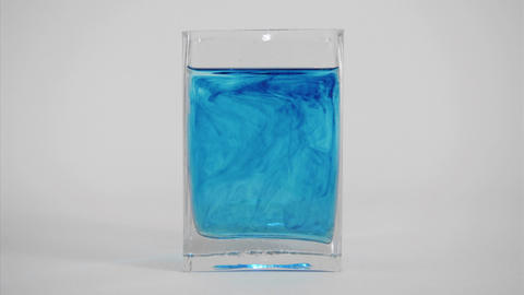 Blue dye diffuses through a glass of water Footage