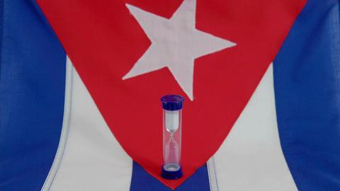 A Cuban flag sits beneath a run hourglass Stock Video Footage