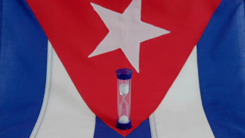 A Cuban flag sits beneath a run hourglass Footage
