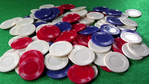 A pile of poker chips on a green felt table Stock Video Footage