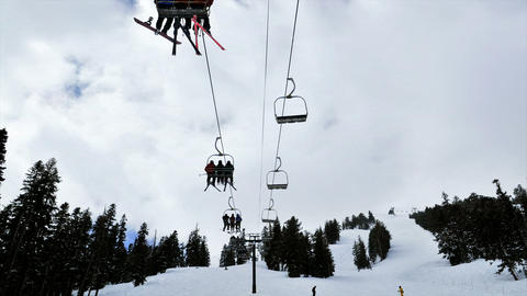 Time-lapse of people riding up a ski lift in the mountains Stock Video Footage