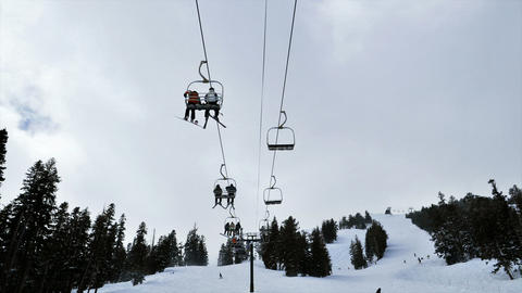 Time-lapse of people riding up a ski lift in the mountains Footage