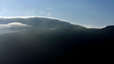 Time-lapse of clouds rolling over mountain top Stock Video Footage