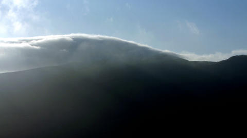 Time-lapse of clouds rolling over mountain top Footage