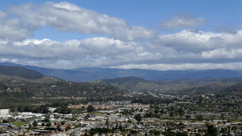 Time-lapse of clouds over city and mountains Stock Video Footage