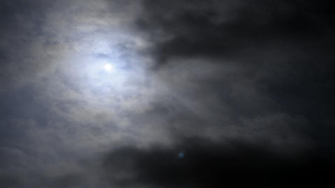 Time lapse clouds with the moon behind them in the night sky Stock Video Footage