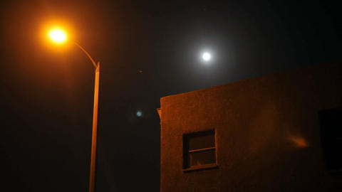 Time lapse of moon rising over a house and street lamp Footage